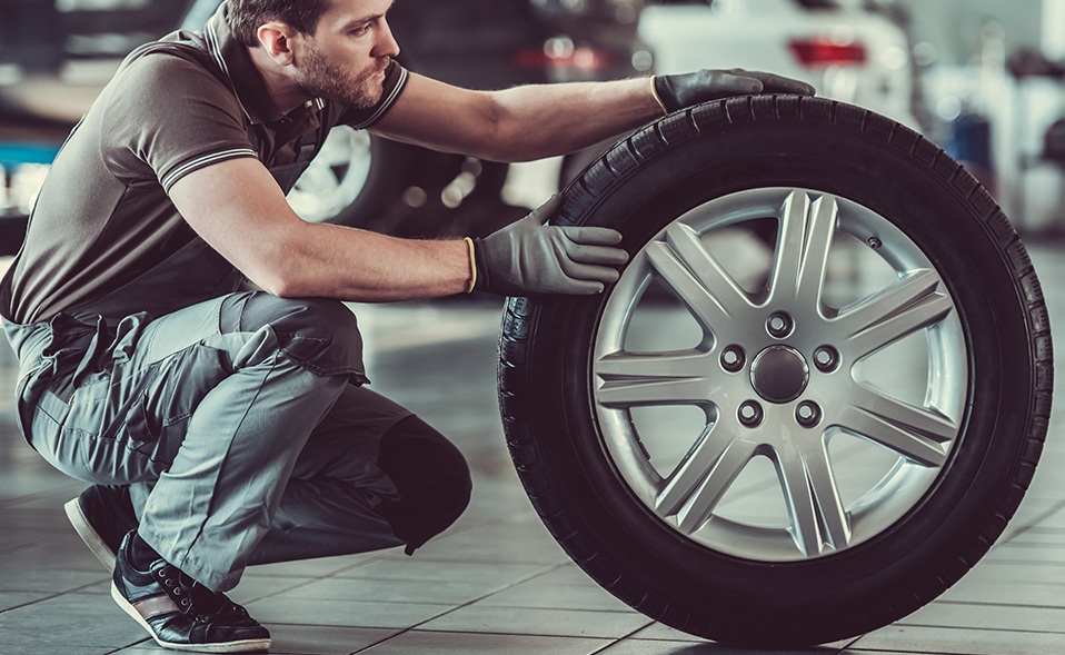 Mechanic holding a tyre - MOT, Servicing & Tyres Swanage
